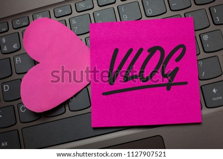 Conceptual hand writing showing Vlog. Business photo text Entertaining multimedia self broadcasting news reporting stories Keyboard grey keys pink paper love idea thought computer hart.