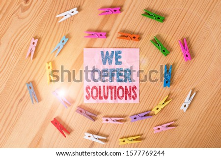 Conceptual hand writing showing We Offer Solutions. Business photo text Offering help assistance Experts advice strategies ideas Colored crumpled papers wooden floor background clothespin. #1577769244