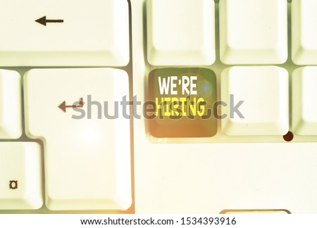 Conceptual hand writing showing We Re Hiring. Business photo text Advertising Employment Workforce Placement New Job White pc keyboard with note paper above the white background.