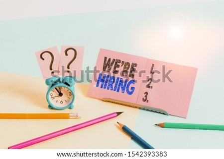 Conceptual hand writing showing We Re Hiring. Business photo text recently employ someone or pay him to do particular job Mini size alarm clock beside stationary on pastel backdrop.