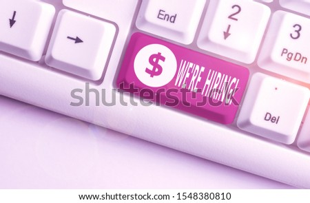 Conceptual hand writing showing We Re Hiring. Business photo text recently employ someone or pay him to do particular job White pc keyboard with note paper above the white background.