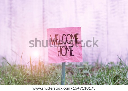 Conceptual hand writing showing Welcome Home. Business photo text a reception usually celebrate the return home of a demonstrating Plain paper attached to stick and placed in the grassy land. Сток-фото ©