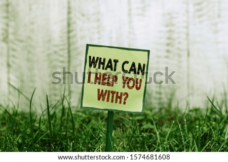 Conceptual hand writing showing What Can I Help You With Question. Business photo showcasing Offering assistance Experts advice ideas Plain paper attached to stick and placed in the grassy land. #1574681608