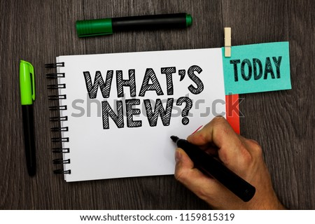 Conceptual hand writing showing What s is New question. Business photo showcasing Asking about latest Updates Trends Happening News Man holding marker notebook reminder cup markers wood table.