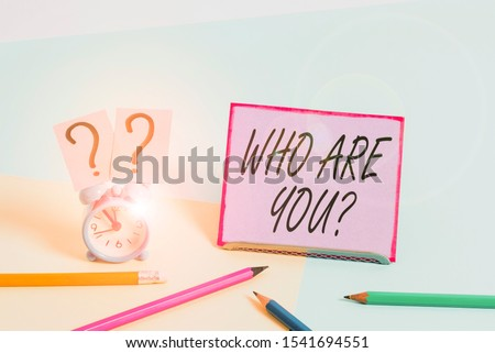 Conceptual hand writing showing Who Are You Question. Business photo showcasing asking about someone identity or demonstratingal information Mini size alarm clock beside stationary on pastel backdrop.