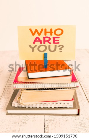 Conceptual hand writing showing Who Are Youquestion. Business photo text someone asking your demonstratingal background or history pile stacked books notebook pin color reminder white wooden.