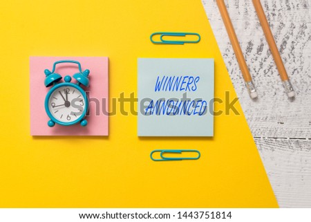 Conceptual hand writing showing Winners Announced. Business photo text Announcing who won the contest or any competition Notepads colored paper sheet markers alarm clock wooden background.