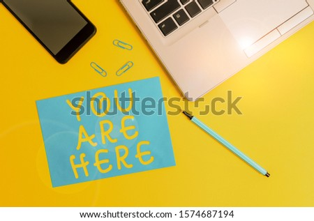 Conceptual hand writing showing You Are Here. Business photo showcasing This is your location reference point global positioning system Trendy open laptop smartphone marker paper sheet clips. #1574687194