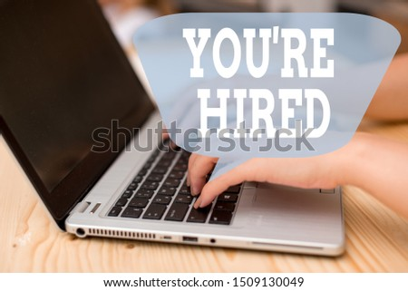 Conceptual hand writing showing You Re Hired. Business photo showcasing New Job Employed Newbie Enlisted Accepted Recruited woman with laptop smartphone and office supplies technology. #1509130049