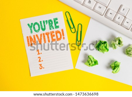 Conceptual hand writing showing You Re Invited. Business photo text make a polite friendly request to someone go somewhere Flat lay with copy space white paper with paper clips on the table. #1473636698
