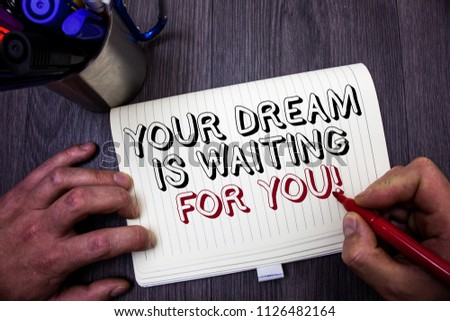 Conceptual hand writing showing Your Dream Is Waiting For You. Business photo showcasing Goal Objective Intention Target Yearning Plan Man hold holding red marker notebook table messages ideas. #1126482164