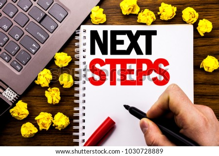 Conceptual hand writing text caption Next Steps. Business concept for Future Golas and Target Written on tablet laptop, wooden background with businessman hand, finger holding PC.