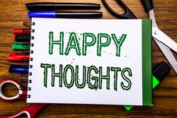 Conceptual hand writing text Happy Thoughts.  Concept for Happiness Thinking Good Written on notebook, wooden background office equipment like pens scissors colourful marker