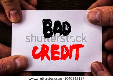 Conceptual hand writing text showing Bad Credit. Concept meaning Poor Bank Rating Score For Loan Finance written Sticky Note Paper Holding Hand with Finger.
