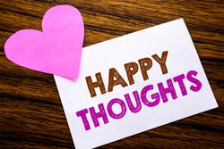 Conceptual hand writing text showing Happy Thoughts. Concept for Happiness Thinking Good written on sticky note paper, wooden background. With pink heart meaning love adoration.