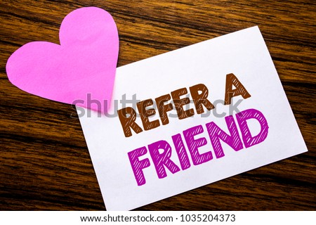 Conceptual hand writing text showing Refer A Friend. Concept for Referral Marketing written on sticky note paper, wooden background. With pink heart meaning love adoration.