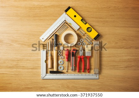 Conceptual house composed of DIY and construction tools on hardwood flooring, top view ストックフォト ©
