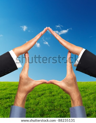 Conceptual house symbol made by hands over bright sunny landscape background. Real estate, housing, construction industry, architecture and design concept. Isolated with clipping path.