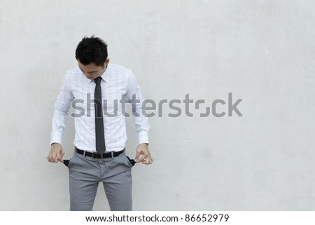 Conceptual image. Asian Businessman stands holding his pockets out showing he has no money.