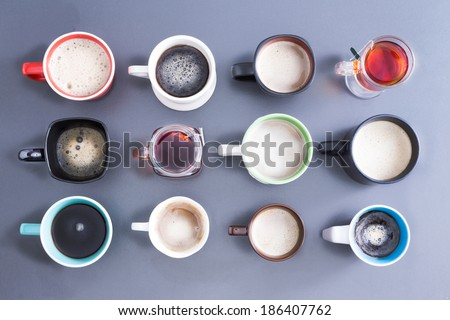 Conceptual image depicting the Time for your daily dose of caffeine with an overhead view of a neat arrangement of twelve different cups, mugs and glasses filled with hot fresh tea and coffee on grey