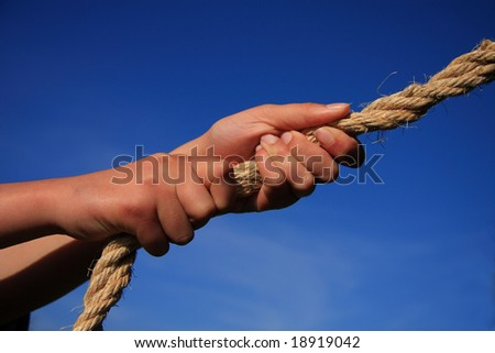 Conceptual image - hands pulling on a rope blue sky background. Might signify strength pulling power determination teamwork etc.