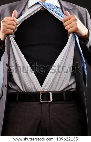 Conceptual image of a businessman tearing off his shirt over gray background