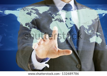 Conceptual image of a businessman using a virtual world map on a touchscreen. Elements of this image furnished by NASA.