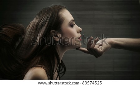 Conceptual image of a hand holding a woman\'s head