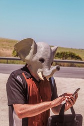 Conceptual image of a modern businessman in an elephant mask symbolizing intelligence and performing human actions eating a sandwich, making a selfie, drinking water, stopping a taxi, making a phone c