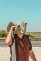 Conceptual image of a young elephant-headed human making a work call with his mobile phone