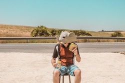 Conceptual image of a young elephant-headed human taking a break from work eating a vegetable sandwich and having a cold drink