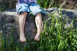 Conceptual image of a young nature lover with a closeup view of the barefoot legs of a little girl dangling over a stone wall with reeds and greenery