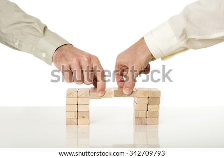 Conceptual image of business merger and cooperation - two male hands joining effort to build a bridge of wooden pegs on a white desk with reflection over white background.