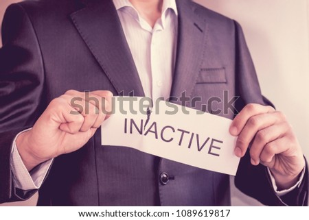 Conceptual image of changing position from inactive to active. Hand holding card with text inactive, tearing off word in.
