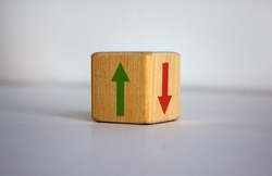 Conceptual image of choice and direction. Wooden cube with arrows pointing in opposite directions. Beautiful white background, copy space.