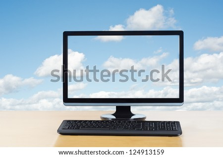 Conceptual image of cloud computing.  Computer monitor and keyboard on light wood table facing viewer,  in front of fluffy white clouds on a blue sky, which also flow unbroken through computer screen.
