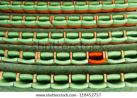 Conceptual image of empty green seats at the theater and one of them is a red - stock photo