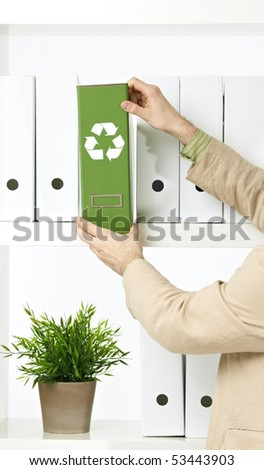 Conceptual image of environmental conservation, businessman holding green folder with recycling symbol.