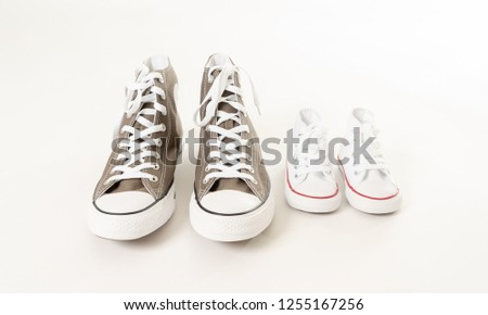 Conceptual image of gumshoes sneakers of father and baby son daughter isolated on white background copy space in single parent family Fathers day Parenting Education and lifestyle concept. #1255167256