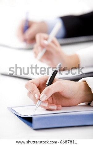 Conceptual image of human hands writing on the paper