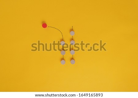 Conceptual image of individuality and uniqueness - red wooden cut circle turning the other direction as the other circles. Over yellow background with copy space.