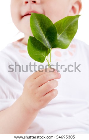 Conceptual image of innocent child holding fresh green leaves