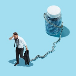 Conceptual image of man bound by a chain with a vial of tablet. Dependence of pills concept. Collage with miniature people. Flat isometric and creative photo