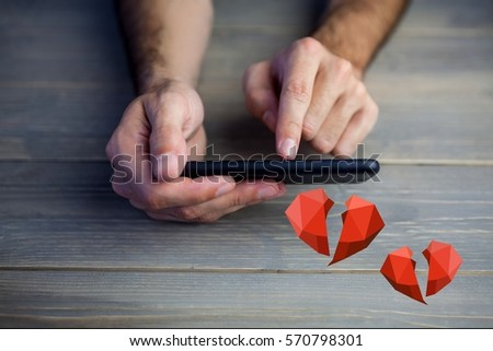 Conceptual image of man hands texting on mobile phone with digital generated red hearts against wooden background #570798301