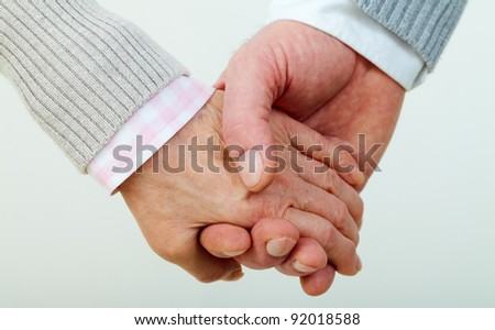 Conceptual image of mature female and male hands together