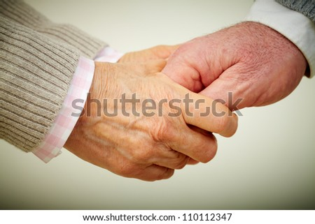 Conceptual image of mature people hands together