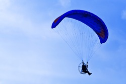Conceptual image of paramotor silhouette in blue sky