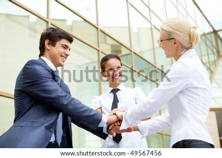 Conceptual image of people making pile of hands and smiling at each other
