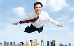 Conceptual image of smiling businessman flying in the clouds