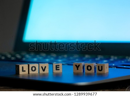 Conceptual image of text Love you in wood blocks on computer with mood romantic screen light background in Valentines day internet connection technology online dating and communication concept.